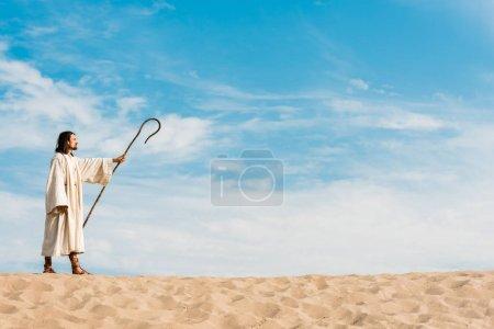 Photo pour Bel homme tenant la canne en bois et debout dans le désert - image libre de droit