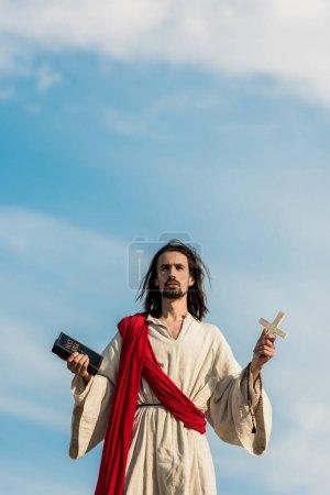Photo pour Jésus retenant la bible sainte et la croix contre le ciel bleu avec des nuages - image libre de droit