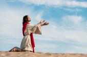 """Постер, картина, фотообои """"Иисус молится на коленях на песке в пустыне против неба"""""""