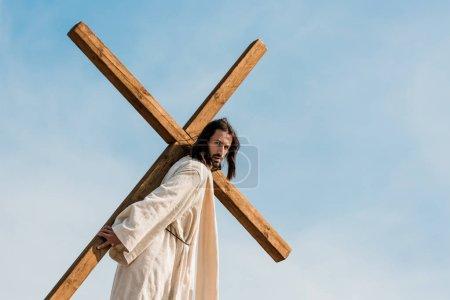 Photo pour Homme barbu marchant avec la croix en bois contre le ciel et les nuages - image libre de droit
