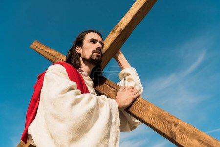 Photo pour Vue d'angle bas de l'homme barbu avec la croix en bois - image libre de droit