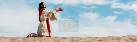Photo for Panoramic shot of jesus praying on knees in desert against sky - Royalty Free Image