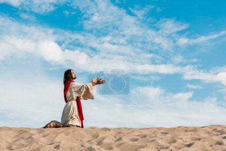 Photo pour Jésus priant sur des genoux dans le désert contre le ciel - image libre de droit