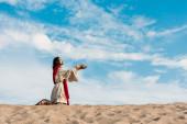 """Постер, картина, фотообои """"Иисус молится на коленях в пустыне против неба"""""""