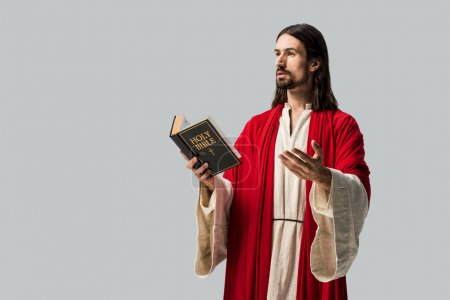 Photo for Handsome man gesturing while holding holy bible isolated on grey - Royalty Free Image