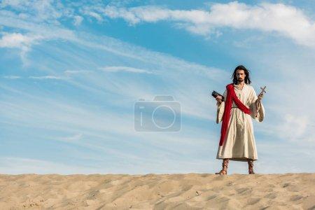 Photo pour Jésus retenant la bible sainte et la croix contre le ciel bleu avec des nuages dans le désert - image libre de droit