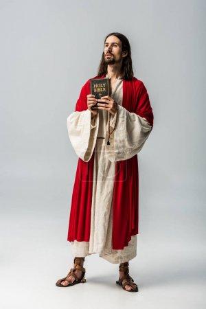 Photo pour Beau homme religieux retenant la bible sainte sur le gris - image libre de droit