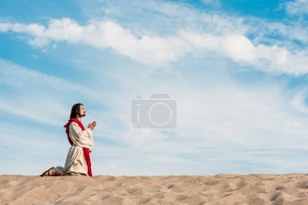 Photo for Man praying on knees in desert against sky - Royalty Free Image