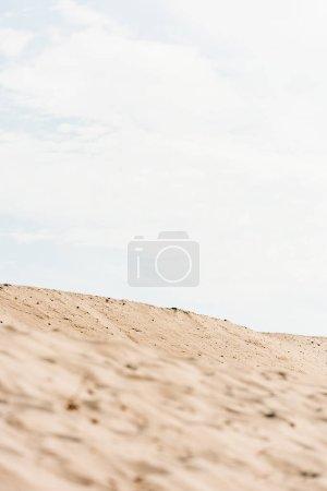 Photo pour Foyer sélectif de sable ondulé et doré contre le ciel avec des nuages dans le désert - image libre de droit