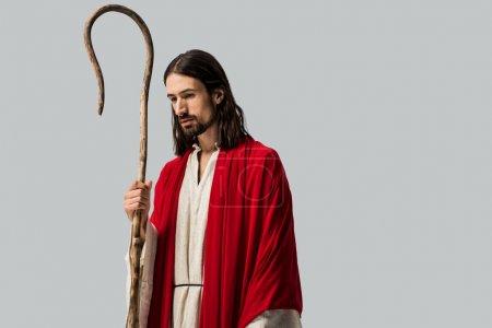 Photo pour Triste homme en robe de Jésus tenant canne en bois isolé sur gris - image libre de droit