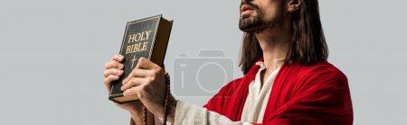 Photo pour Plan panoramique de Jésus tenant la bible sacrée isolée sur gris - image libre de droit