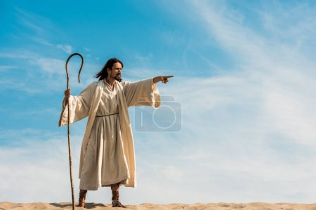Photo for Bearded man holding wooden cane and pointing with finger in desert against sky - Royalty Free Image