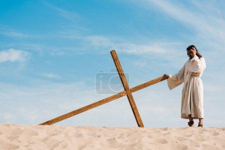 Photo pour Homme barbu debout près de croix en bois dans le désert sur le sable - image libre de droit