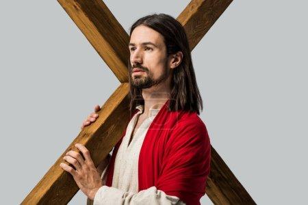 Photo pour Jésus retenant la croix en bois d'isolement sur le gris - image libre de droit