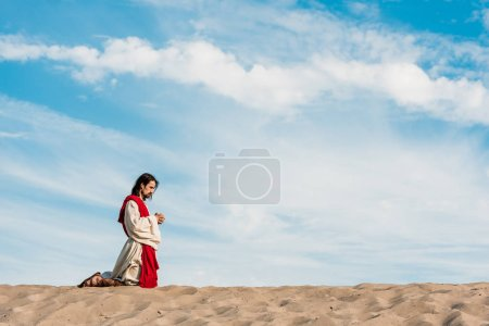 Photo pour Homme priant sur des genoux avec les mains serrées dans le désert - image libre de droit