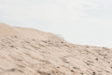 selective focus of wavy sand against sky with clouds in desert