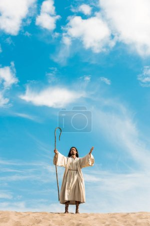 Photo pour Handsome bearded man holding wooden cane and standingin desert against sky - image libre de droit