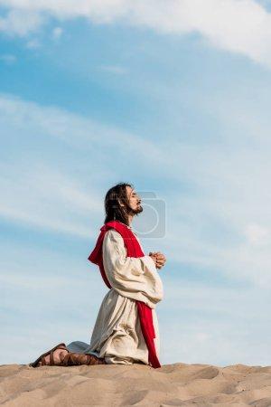 Photo pour Jésus priant les yeux fermés dans le désert contre le ciel bleu - image libre de droit