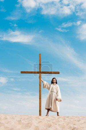Photo pour Homme barbu debout avec croix en bois dans le désert sur le sable - image libre de droit