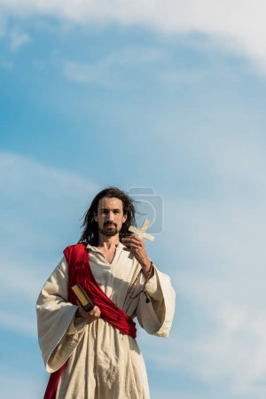 Photo for Jesus holding holy bible and cross against blue sky outside - Royalty Free Image