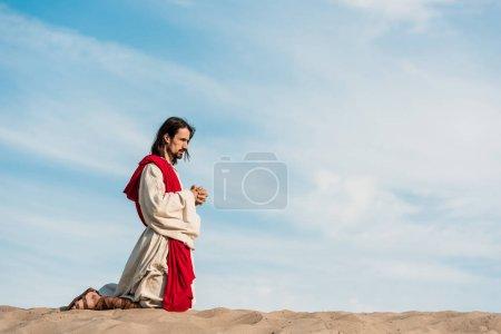 Photo pour Jésus priant à genoux les mains serrées dans le désert contre le ciel bleu - image libre de droit
