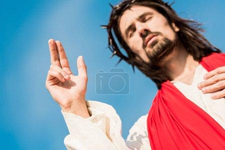 Photo pour Vue d'angle bas de l'homme avec les yeux fermés faisant des gestes contre le ciel bleu - image libre de droit