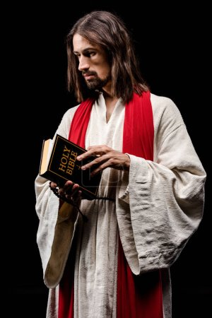 Photo for Handsome man holding holy bible isolated on black - Royalty Free Image