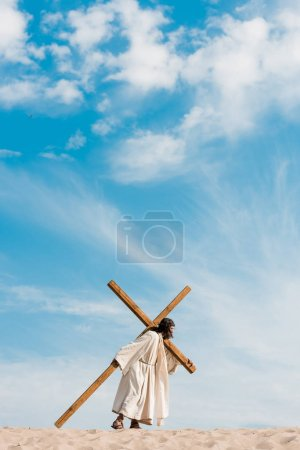 Photo for Bearded man walking with wooden cross in desert on golden sand - Royalty Free Image