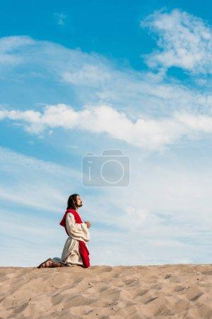 Photo pour Homme priant sur des genoux avec les mains serrées dans le désert avec le sable ondulé - image libre de droit