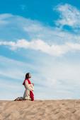 """Постер, картина, фотообои """"человек молится на коленях с сжатыми руками в пустыне с волнистым песком"""""""