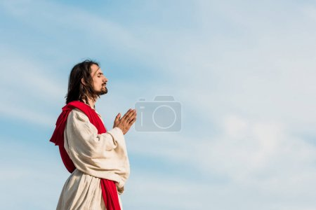 Photo for Man with closed eyes praying against blue sly - Royalty Free Image