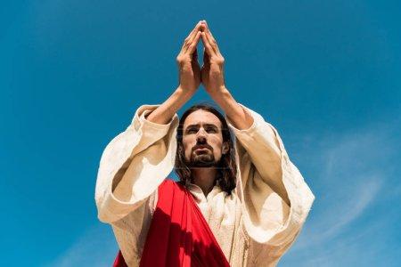 Photo pour Vue d'angle bas de Jésus avec des mains de prière contre le ciel bleu - image libre de droit