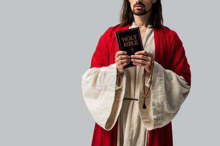 Photo for Cropped view of religious man in jesus robe holding holy bible isolated on grey - Royalty Free Image