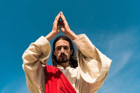 Photo pour Vue à angle bas de Jésus avec la prière et en regardant la caméra contre le ciel bleu - image libre de droit