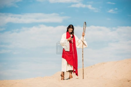 Photo for Handsome man in jesus robe holding wooden cane and using smartphone in desert - Royalty Free Image