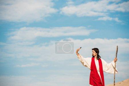 Photo pour Bel homme dans la robe de jésus parlant selfie tout en retenant la canne en bois - image libre de droit