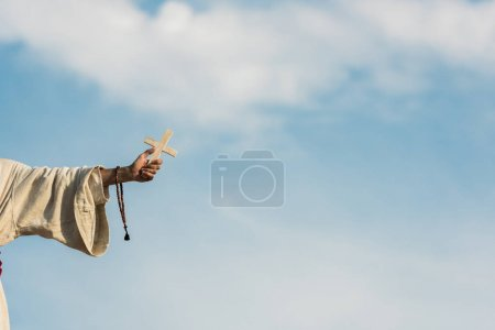 Photo for Cropped view of religious man holding cross and rosary beads against blue sky - Royalty Free Image
