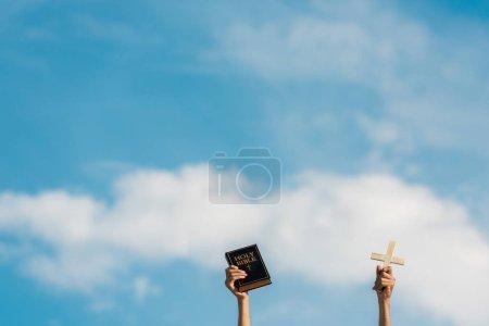 Photo pour Vue recadrée de l'homme retenant la bible sainte et la croix contre le ciel bleu avec des nuages - image libre de droit