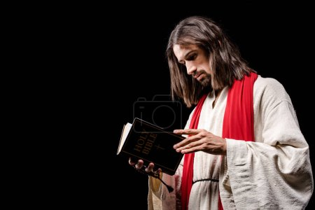 Photo for Religious man holding book with holy bible lettering isolated on black - Royalty Free Image