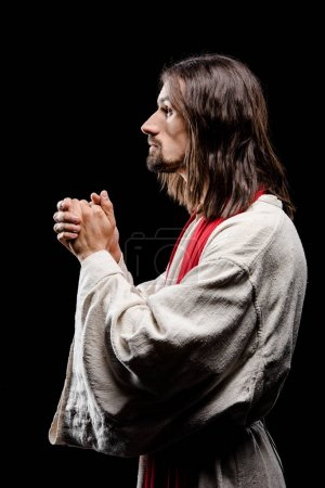 Photo for Side view of bearded man praying with clenched hands isolated on grey - Royalty Free Image