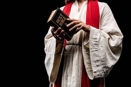 Photo pour Vue recadrée de livre de fixation d'homme avec le lettrage sacré de bible d'isolement sur le noir - image libre de droit