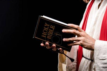 Photo pour Vue recadrée du livre de fixation d'homme avec les lettres saintes de bible d'isolement sur le noir - image libre de droit