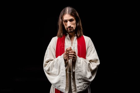 Photo for Religious man holding rosary beads isolated on black - Royalty Free Image