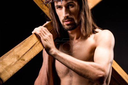 Photo for Religious and shirtless man in wreath with spikes holding wooden cross isolated on black - Royalty Free Image
