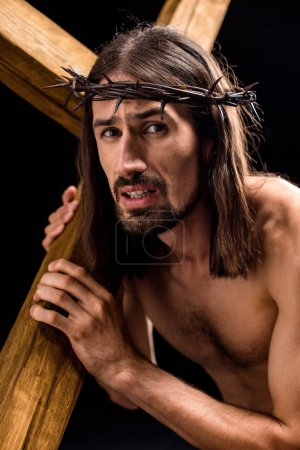 Photo for Shirtless man in wreath with spikes holding wooden cross isolated on black - Royalty Free Image