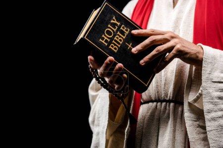 vista recortada del hombre religioso sosteniendo el libro con las letras sagradas de la biblia aisladas en negro