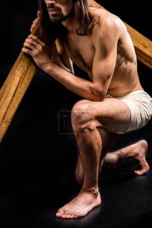 Photo pour Vue recadrée de l'homme torse nu retenant la croix sur le noir - image libre de droit
