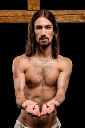 Photo pour Jésus avec des mains sanglantes debout près de croix en bois isolé sur noir - image libre de droit