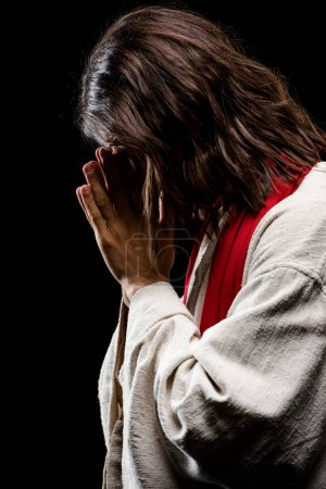 Photo for Man covering face while praying isolated on black - Royalty Free Image
