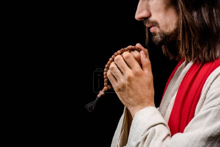 Photo for Side view of man holding rosary beads isolated on black - Royalty Free Image